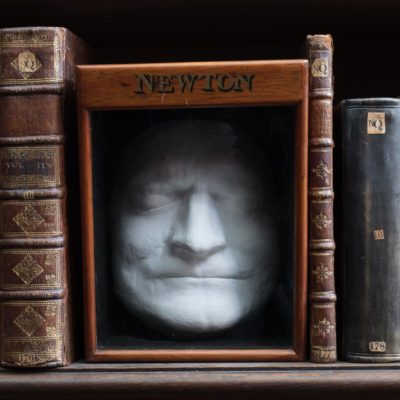 Isaac Newton's Death Mask sitting on a shelf in the Wren Library, Trinity College, Cambridge and nestled between some of Newton's personal books.